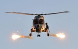 A Lynx helicopter fires flares over HMS Monmouth