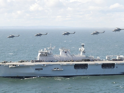 Five RN Lynx helicopters flying past HMS Ocean before embarking to support the Olympic security effort