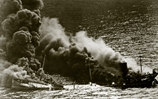 A tanker sinks after a torpedo from a U-boat breaks its back