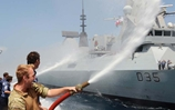 AB(SEA) Lee Tague is among HMS Monmouth Ship's company who, in keeping with tradition, use firehoses as a ceremonial salute to HMS Dragon during the sail past.