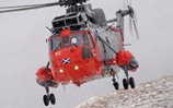 One of HMS Gannet's Sea Kings flies through a snow flurry in the Highlands